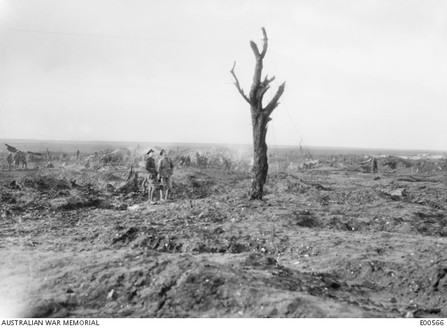Black and white photo of two soldiers looking at lone tree at Mouquet Farm amid the battlefield destruction.