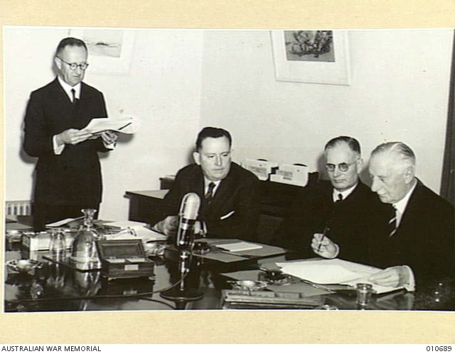 The Governor General, Lord Gowrie, reading the proclamation announcing that Australia is at war with Japan.  From left, the Secretary Prime Minister's Department, Mr F Strahan; Minister for the Army, Mr Forde; Prime MInister Mr Curtain; and Lord Gowrie.