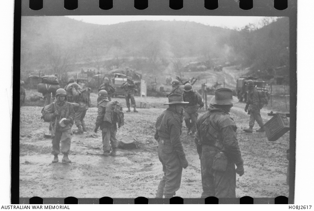 The 3rd Battalion, The Royal Australian Regiment (3RAR), in Korea, is being relieved by troops of the 20th Battalion, Philippines Regimental Combat Team. The Australians have been involved in fighting in the Battle of Maryang San and an area near the Imjin River. In a camp beside a valley, two unidentified soldiers from 3RAR stand in the mud and watch the newly arrived members of the 20th Battalion acclimatise to the camp. Photo circa 23 November 1951